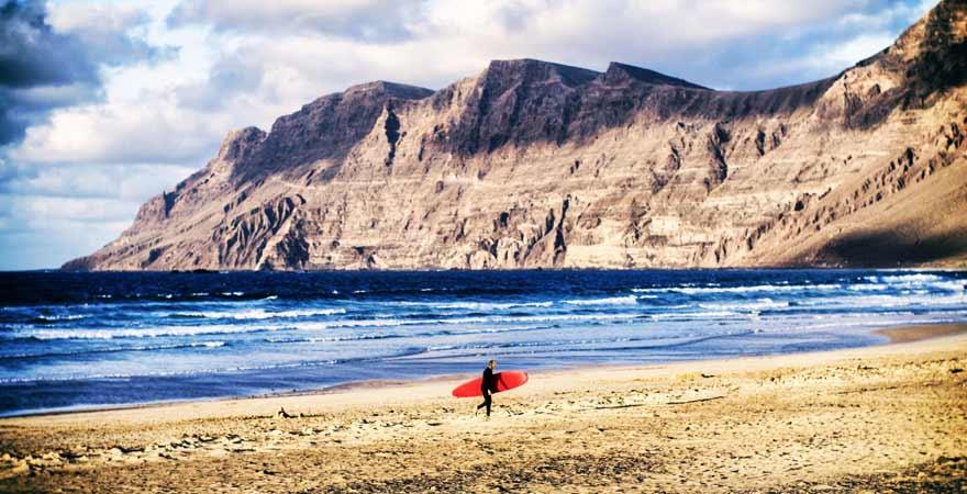 Surfer am Strand Celeta de-Famara auf Lanzarote in Spanien