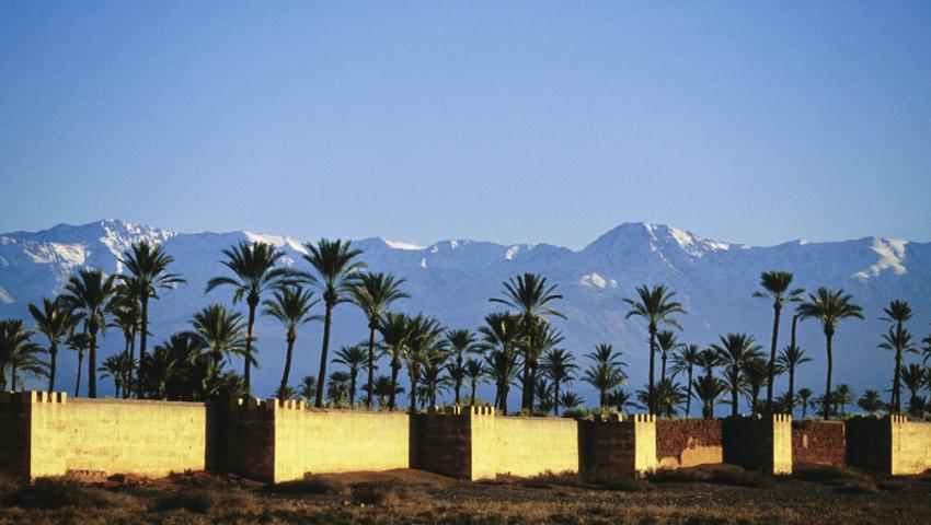 Stadtmauer in Marrakesch mit Atlas-Gebirge im Hintergrund.