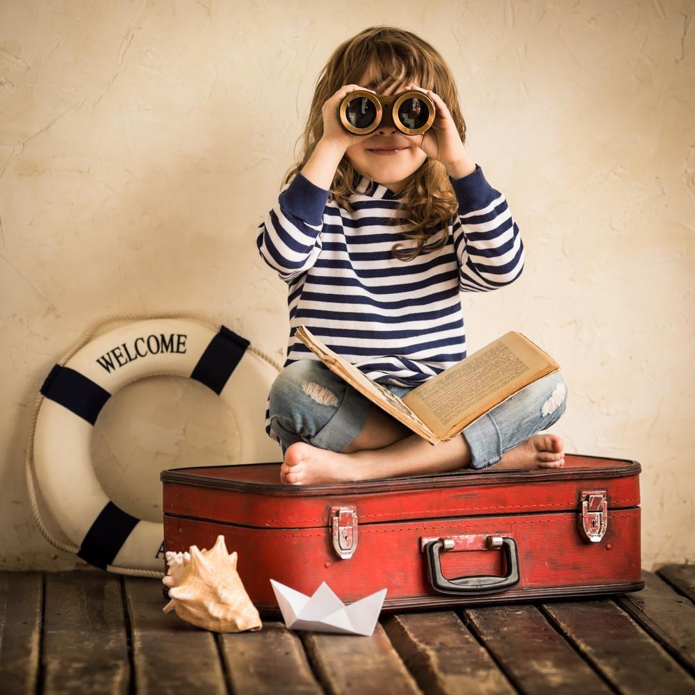 maedchen auf gepacktem koffer