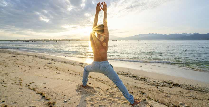 Mann der Yoga am Strand macht