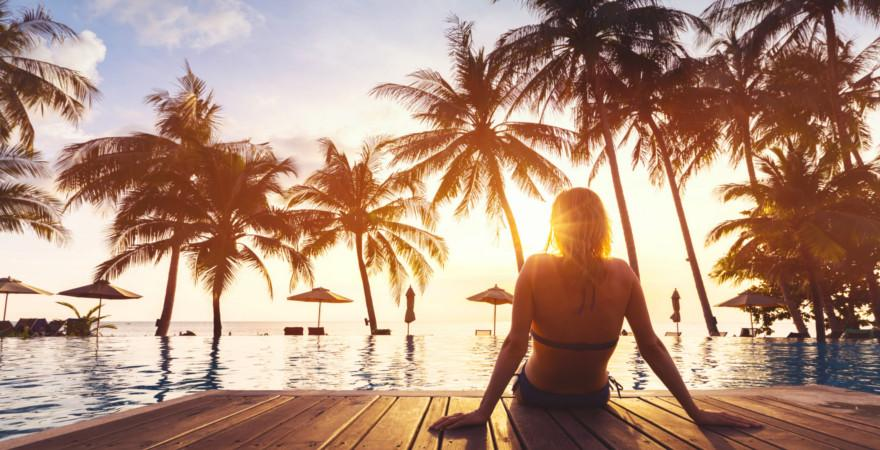 Frau an einem Pool bei Sonnenuntergang