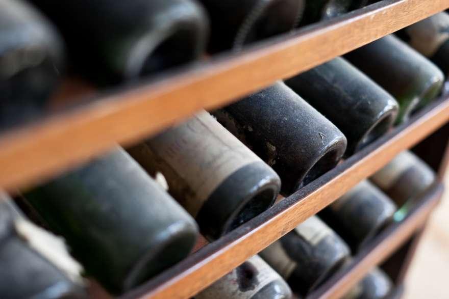 Weinregal mit verstaubten Weinflaschen